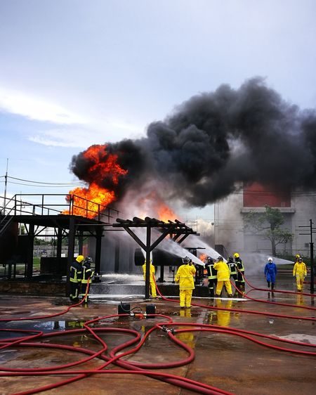 Firefighters dousing fire against sky