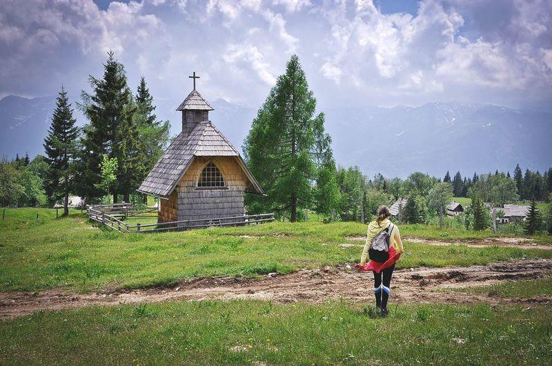 Full length rear view of woman walking on grassy field by chapel against sky