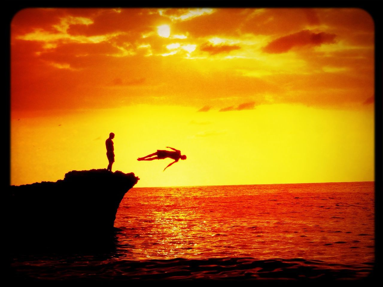 People diving into sea at sunset