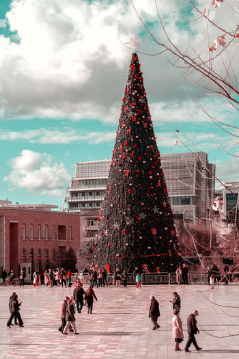 People on christmas tree against buildings in city