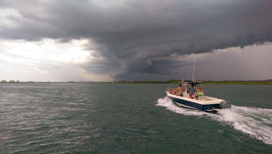 Motorboat in sea against cloudy sky