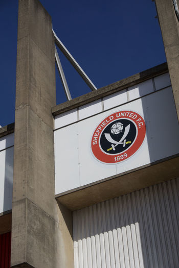 Team logo on stand exterior at Bramall Lane Football Ground, Sheffield United. Sheffield Sheffield United Bramall Lane Football Stadium Ground Standing Yorkshire Blades Clear Blue Sky Sunny Summer Architecture Built Structure Low Angle View Sky Sign Text No People Day Western Script Clear Sky Information Sign Outdoors Building Exterior Blue Building Script