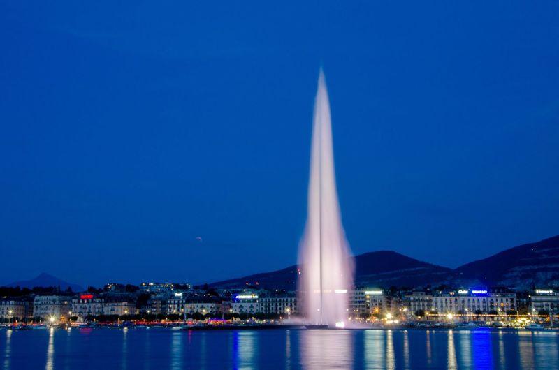 Illuminated city against clear blue sky