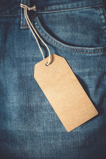 High angle view of blank label hanging on jeans