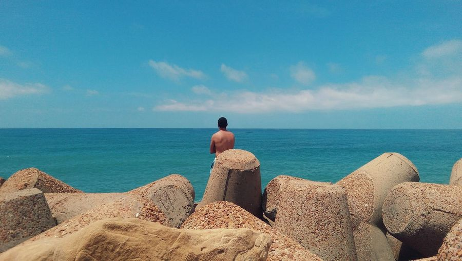 Rear View Of Shirtless Man On Tetrapods At Sea Shore Against Sky
