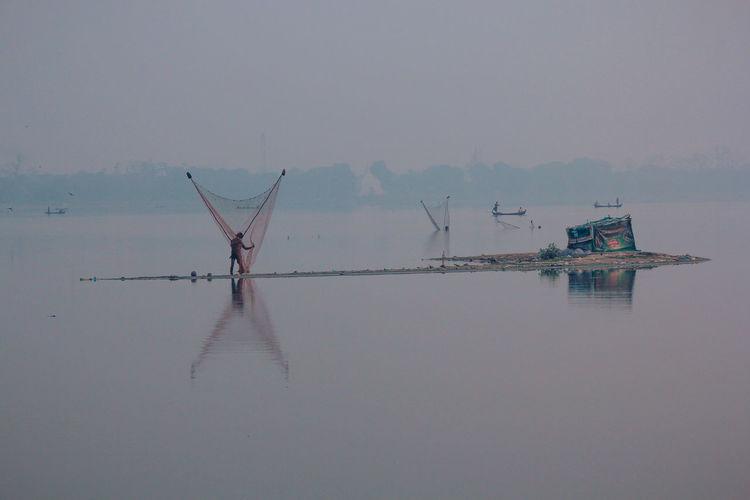 Rear View Of Man Arranging Fishing Net In Lake