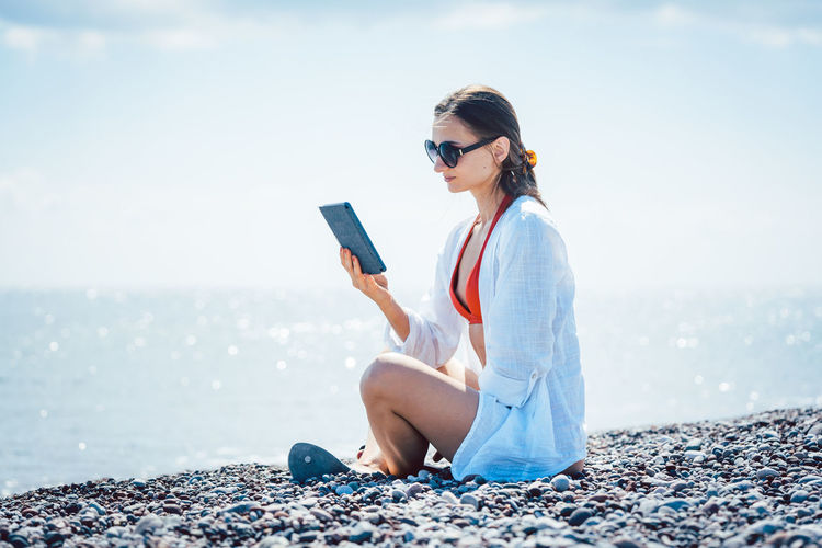 Woman reading an electronic book relaxing on the beach Beach Life Pebble Beach Reading Woman Beach Book Ebook Ocean Realxing Relax Sea Sunshine Swimwear Vacation Water