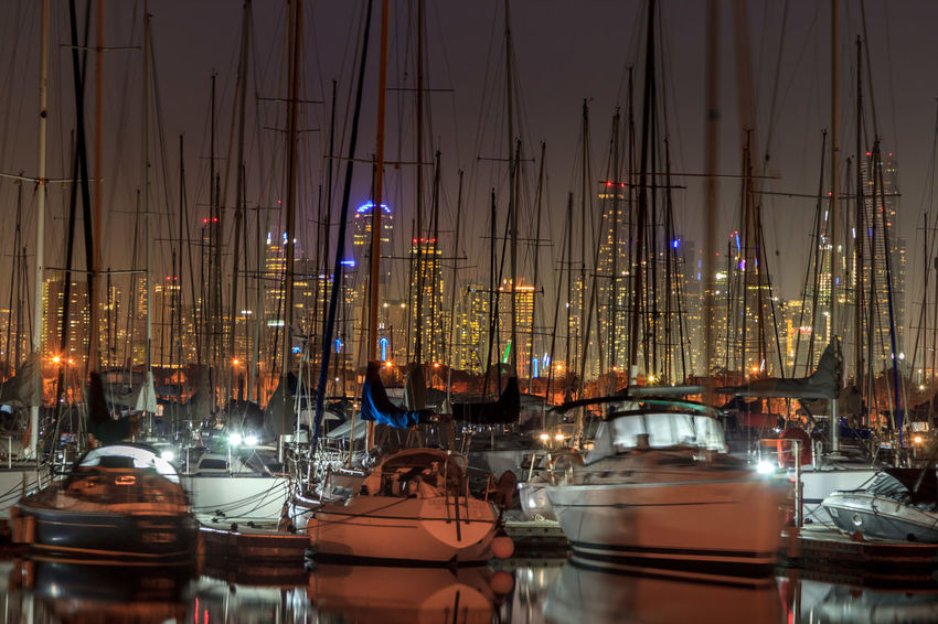 Masts of boats with the city in the background Architecture Building Building Exterior Built Structure City Glowing Harbor Illuminated Mast Mode Of Transportation Nature Nautical Vessel Night No People Outdoors Reflection Sailboat Sky Transportation Water