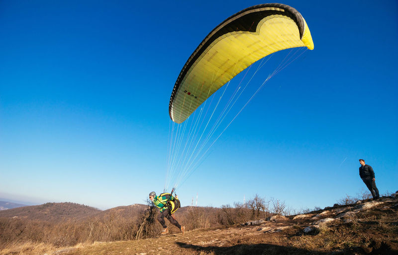 Adult Adults Only Adventure Blue Clear Sky Day Extreme Sports Hot Air Balloon Landscape Leisure Activity Low Angle View Nature One Man Only One Person Only Men Outdoors Parachute People Scenics Sky
