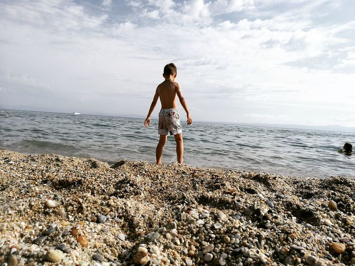 Rear view shirtless boy standing on shore at beach