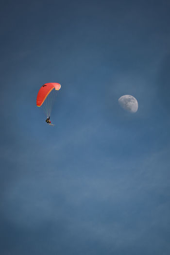 Paraglider next to moon Sky Moon Low Angle View Flying Adventure Beauty In Nature Paragliding Cloud - Sky Mid-air Nature Parachute Sport Extreme Sports Outdoors Unrecognizable Person Scenics - Nature Transportation Day Blue Freedom Planetary Moon