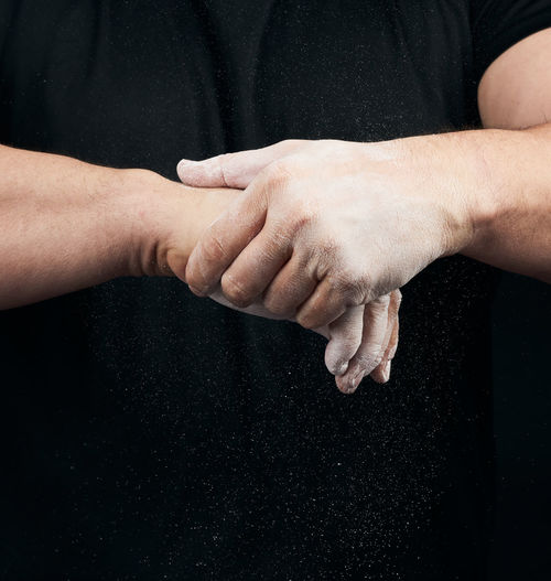 Midsection of hand holding hands