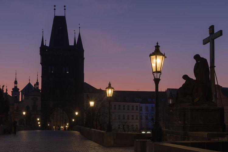 Illuminated charles bridge in prague just before sunrise