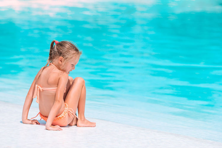 Woman sitting by swimming pool in sea