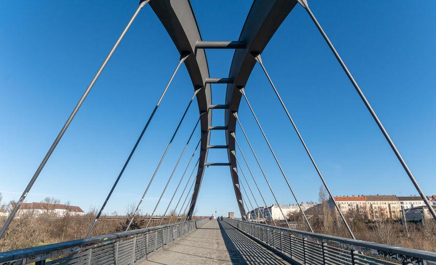 View of suspension bridge against clear blue sky