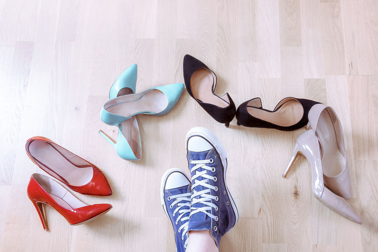 Low section of women with shoes on wooden floor