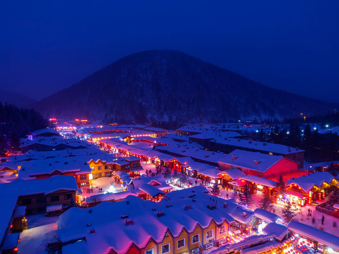 High angle view of illuminated snow covered houses in town