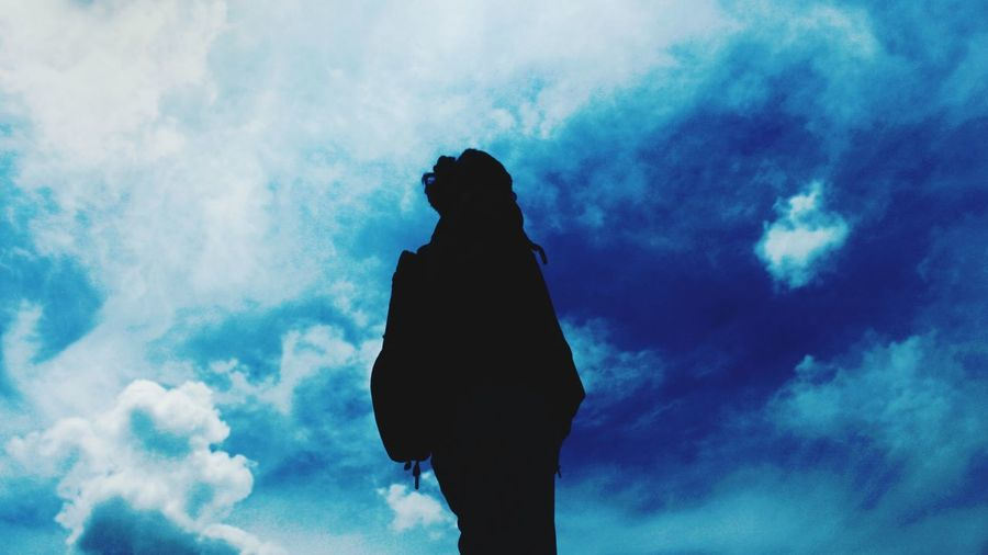 Low angle view of silhouette woman standing against blue sky