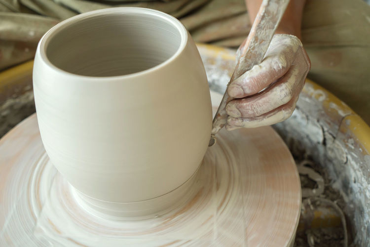Cropped hand of woman making pottery in workshop