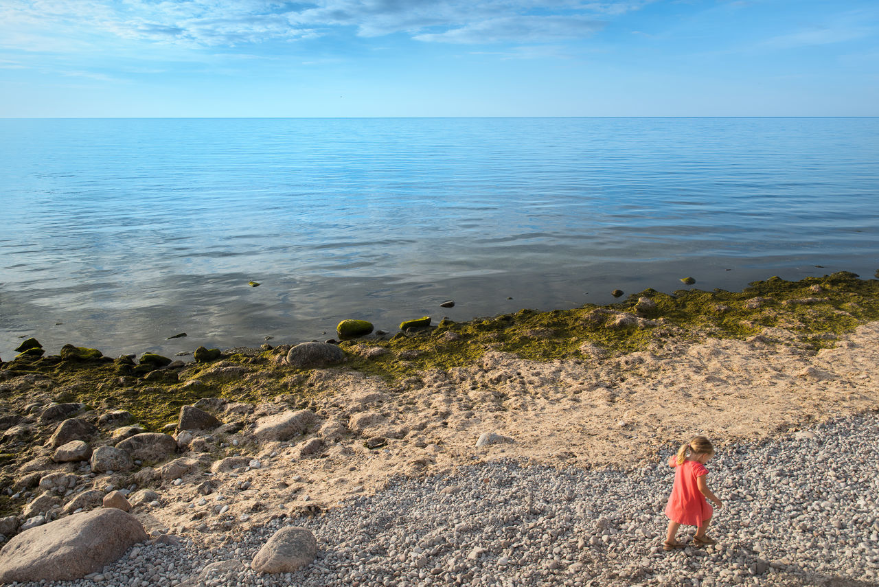 sea, horizon over water, water, nature, sky, beach, rock - object, day, beauty in nature, outdoors, scenics, tranquility, one person, real people, tranquil scene, standing, full length, people