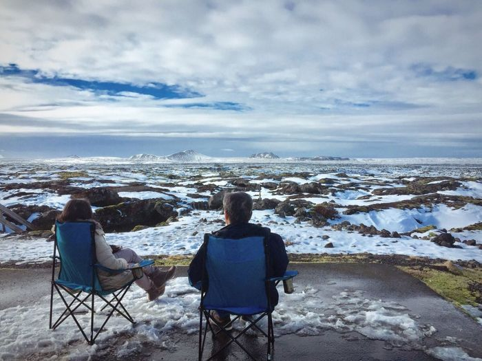 Rear view of people sitting on camping chair during winter