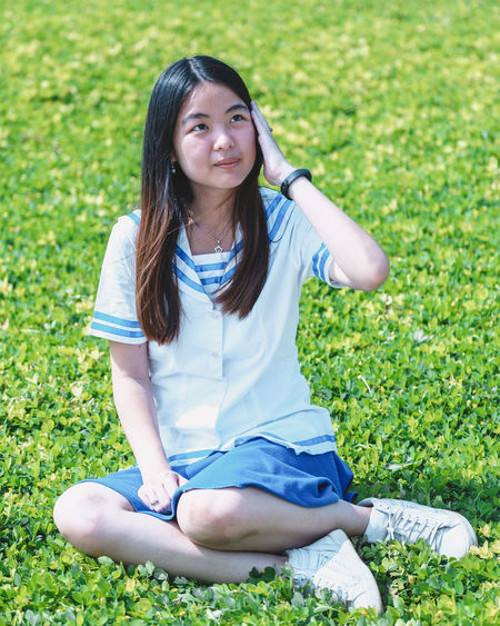 Sitting Full Length Grass One Person Casual Clothing Real People Plant Cross-legged Nature Front View Leisure Activity Field Looking At Camera Lifestyles Women Girls Day Portrait Childhood Hair Hairstyle Outdoors Innocence
