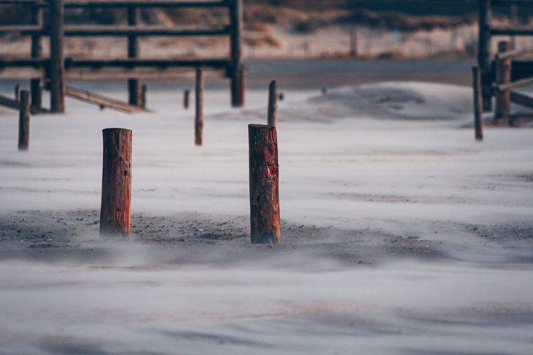Wooden post on snow covered land