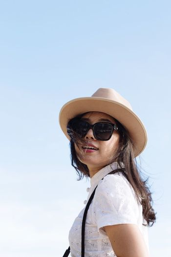 Portrait of young woman wearing sunglasses standing against clear sky