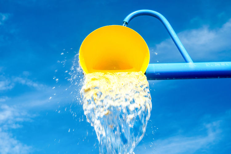 Wet yellow buckets of fun at the water park. Outdoors Outdoor Park Park - Man Made Space Background Trees Low Angle View Low Angle Water Spilling Water Tree Leaves Summer Summertime Fun Water Yellow Splashing Blue Colored Background Drop Close-up Water No People Day
