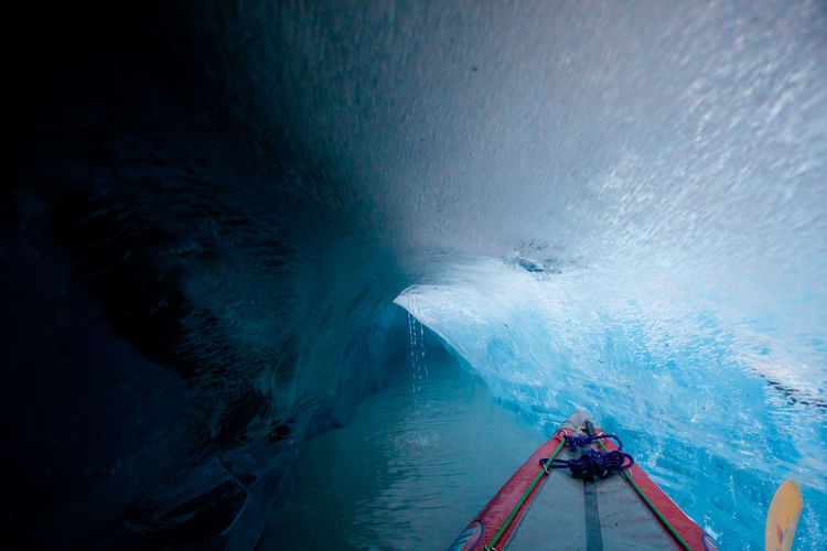 Cropped image of boat on sea in ice cave