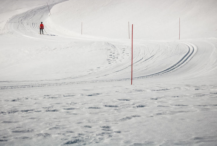 View of people skiing on snow covered land