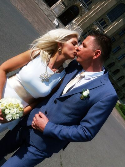 Tilt image of newlywed couple kissing on road