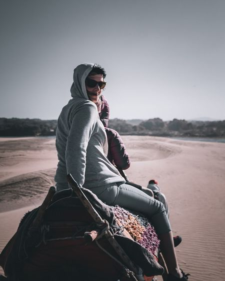 Portrait of mother with daughter riding on camel at desert