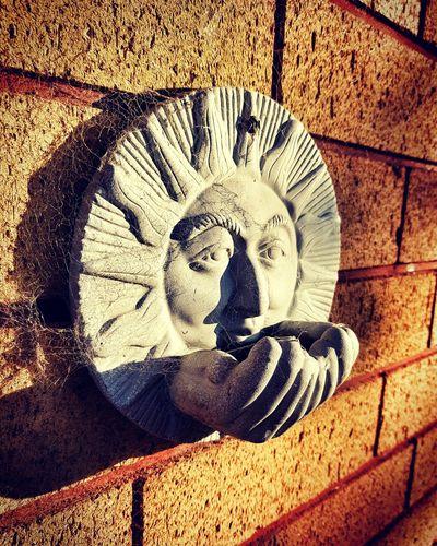 A visual echo of the ancient Sun god, Helios, hangs on a wall lit by the setting sun..... New Zealand NZ Helios Sun God  Brick Brick Wall Sunset