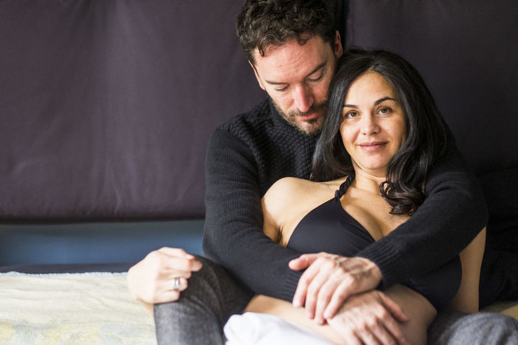 romantic and sweet scene with nice couple she pregnant on the bed in the morning Family Love Adult Arm Around Bonding Couple - Relationship Emotion Front View Furniture Happiness Heterosexual Couple Indoors  Lifestyles Love Mature Men Men Portrait Positive Emotion Pregnant Sitting Smiling Togetherness Two People Waiting For A Baby Women