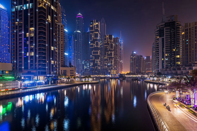 Night city dubai in uae. illuminated buildings by river against sky in city at night
