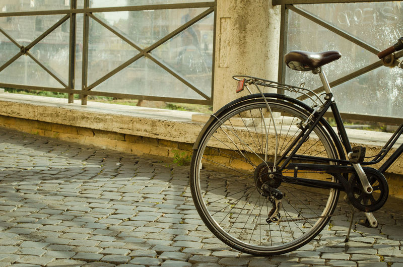 Cropped image of bicycle parked by railing on cobbled street
