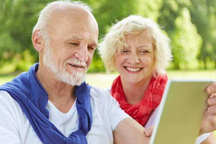 Smiling Senior Couple Using Digital Tablet Against Trees