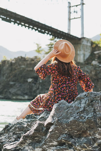 Young woman in dress and felt hat on horochowski bridge on katun river, altai