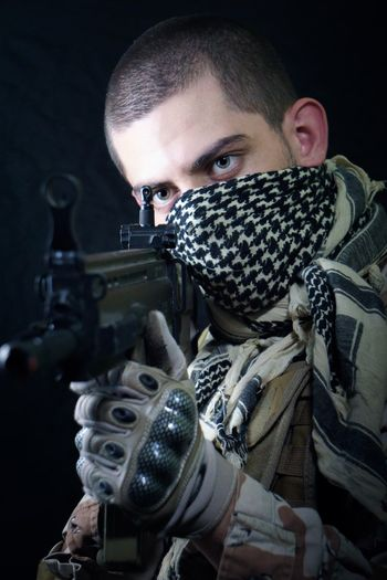 Close-Up Of Man With Shotgun Standing Against Black Background