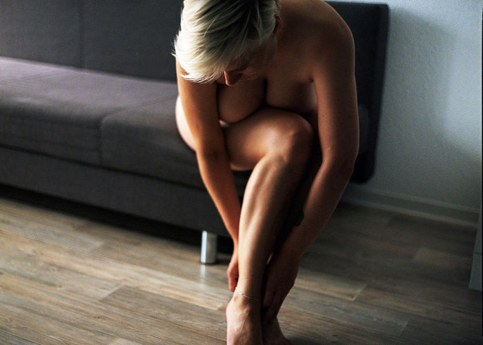 Midsection of woman sitting on floor at home
