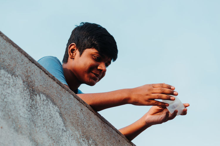 Low angle view of boy holding bottle on terrace against clear sky