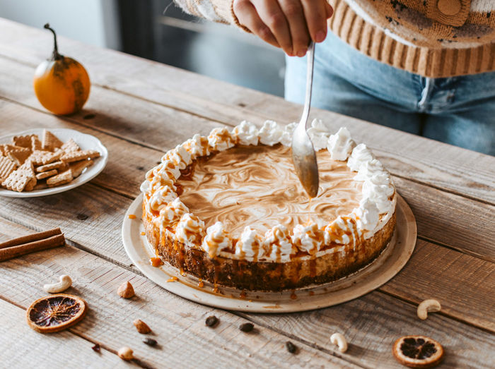 Close-up of woman baking cake. whipped cream, pumpkin pie, caramel.