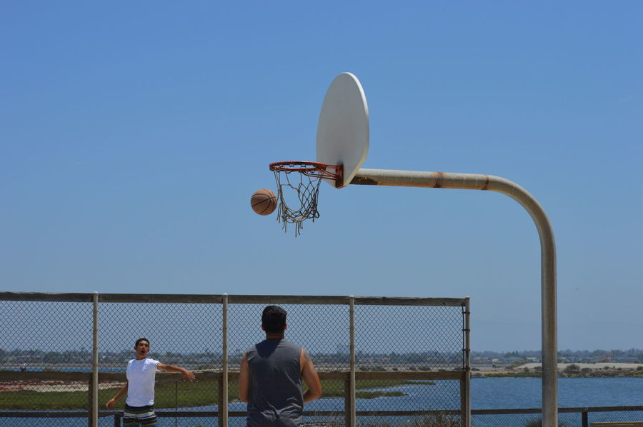 Adult Basketball - Sport Basketball Hoop Basketball Player Clear Sky Court Day Leisure Activity Lifestyles Men Mid-air Outdoors People Playing Practicing Real People Sky Sport Sports Clothing Sports Team Sportsman Team Sport Young Adult