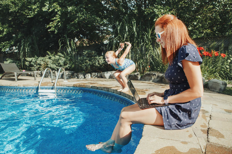 Side view of woman using laptop while girl jumping in swimming pool