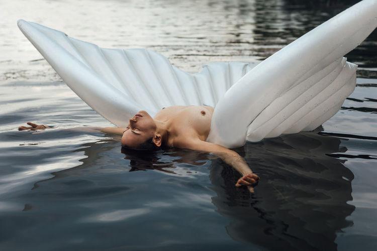 Young woman lying in swimming pool
