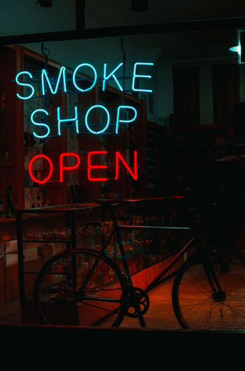 Smoke Shop Neon Sign Architecture Bicycle Building Exterior Built Structure Capital Letter City Communication Illuminated Information Information Sign Mode Of Transportation Neon Night Nightlife No People Sign Store Streetphotography Text Transportation Western Script Wheel Window