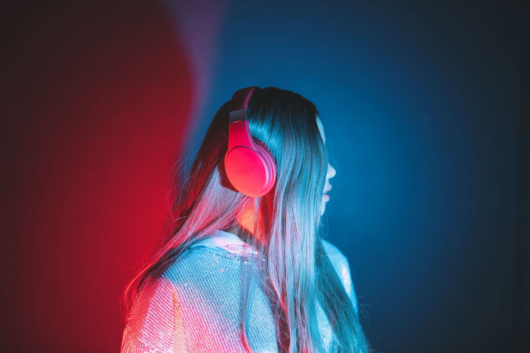 Woman wearing headphones standing against illuminated background