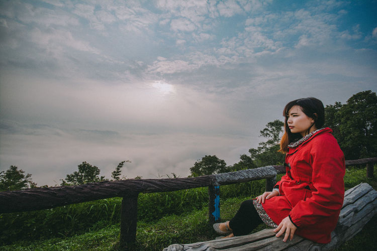 Young woman sitting by railing against cloudy sky