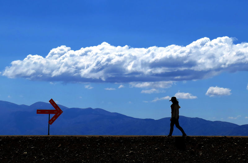 Silhouette woman walking on field against mountain ranges